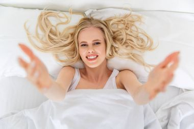top view of beautiful young woman reaching hands and smiling at camera while lying in bed