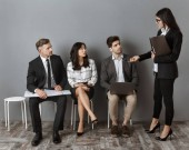 businesswoman choosing one of colleagues for job interview on sits against grey wall