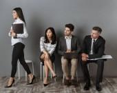 s úsměvem kavkazské podnikatelka na pracovní pohovor a multietnickou kolegy na židlích při pohledu na ni
