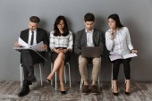 multiethnic business people with digital devices and folders waiting for job interview