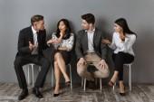 Fotografie Interracial Geschäftsleute in Abendgarderobe mit Gespräch zusammen während des Wartens auf Job-interview
