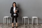 Lächelnde Geschäftsfrau im Anzug mit Laptop wartet auf Vorstellungsgespräch