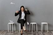 Fotografie wütend und gestresste geschäftsfrau in Anzug mit umschlossenen Papiere warten auf Job-interview