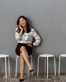 Fotografie lächelnde asiatische geschäftsfrau sprechen auf Smartphone während des Wartens auf Job-interview