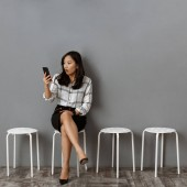 Fotografie emotional asian businesswoman with smartphone waiting for job interview