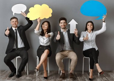 multiethnic business people with paper chat bubbles and arrow showing thumbs up while waiting for job interview