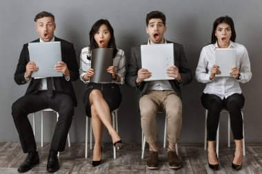 shocked multicultural business people with folders and notebooks waiting for job interview