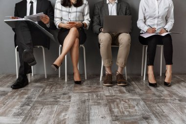 partial view of business people with digital devices and folders waiting for job interview