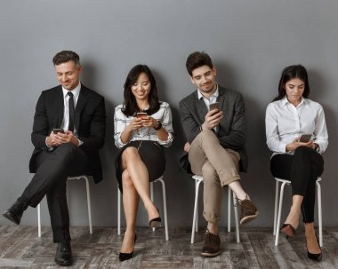 smiling interracial business people in formal wear using smartphones while waiting for job interview