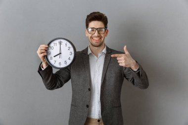portrait of smiling businessman pointing at clock in hand and looking at camera on grey wall background