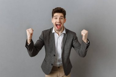 portrait of excited businessman gesturing and looking at camera against grey wall background