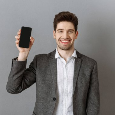 Portrait of smiling businessman showing smartphone with blank screen in hand against grey wall background stock vector