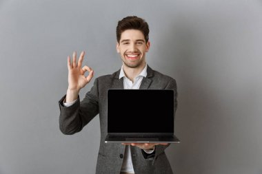 portrait of smiling businessman in suit with laptop with blank screen showing ok sign against grey wall background