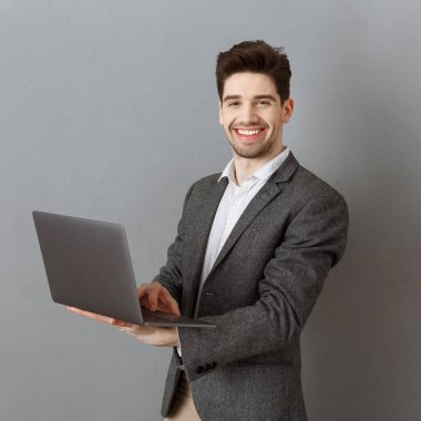 smiling businessman in suit with laptop against grey wall background