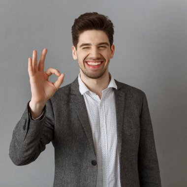 portrait of smiling businessman in suit showing ok sign against grey wall