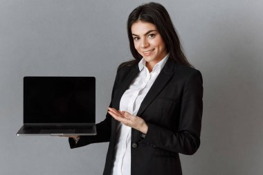 smiling businesswoman pointing at laptop with blank screen against grey wall background