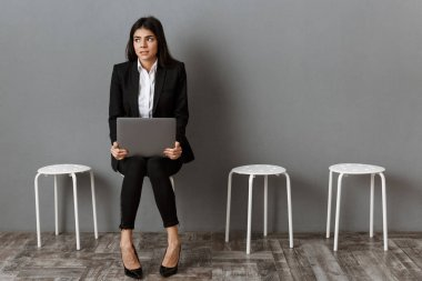 scared businesswoman in suit with laptop waiting for job interview