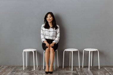 Smiling asian businesswoman sitting on chair while waiting for job interview stock vector