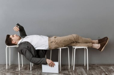 tired businessman with documents checking time while lying on chairs and waiting for job interview