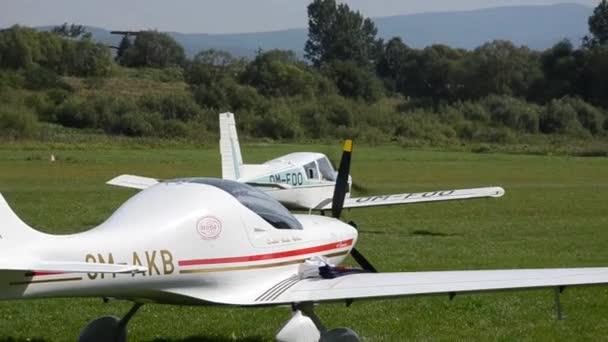 Bílé čtyři sedadla vrtulové Zlín Z43 letadlo pohybuje na trávě přistávací dráha v malé letiště arround stání letadel