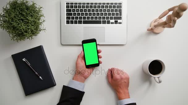 A Mans kezében tartja a telefont egy zöld képernyő