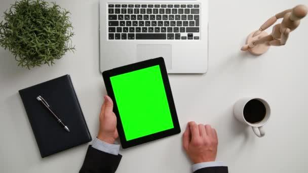 A Mans kezében tartja az i-Pad, egy zöld képernyő