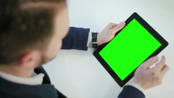 ein Mann, der ein iPad mit grünem Bildschirm benutzt