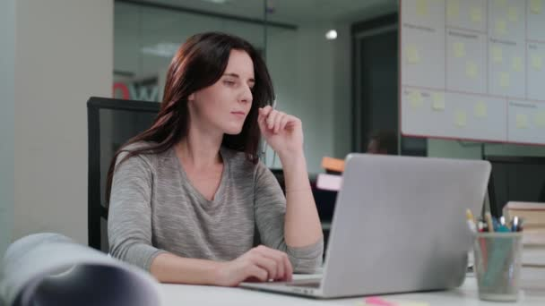 A Lady Sitting in the Office Working on a Laptop