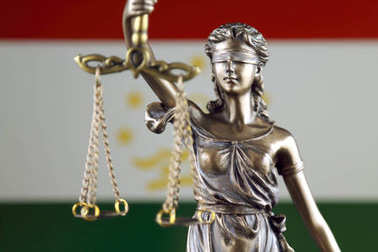 Symbol of law and justice with Tajikistan Flag. Close up.