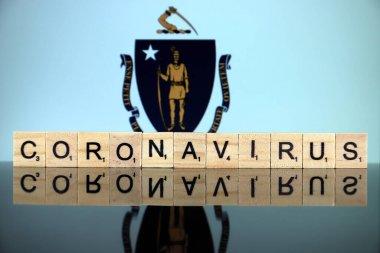 WROCLAW, POLAND - 28 Mart 2020: söz CORONAVIRUS ahşap harflerden yapılmış, ve arka planda Massachusetts Eyalet Bayrağı. Coronavirus (COVID-19) küresel hastalık 2020.