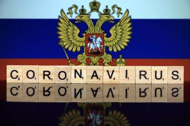 WROCLAW, POLAND - 28 Mart 2020: söz CORONAVIRUS ahşap harflerden yapılmış, ve arka planda Rusya Bayrağı. Coronavirus (COVID-19) küresel hastalık 2020.