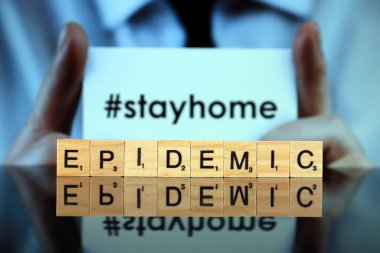 WROCLAW, POLAND - MARCH 30, 2020: The word EPIDEMIC made of wooden letters, and man holding a business card with the words STAY HOME (with hashtag, popular on social media) in the background.