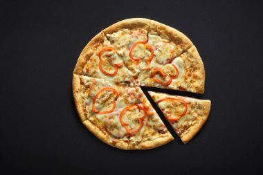 Pizza with ham pepper and cheese on a black stone background
