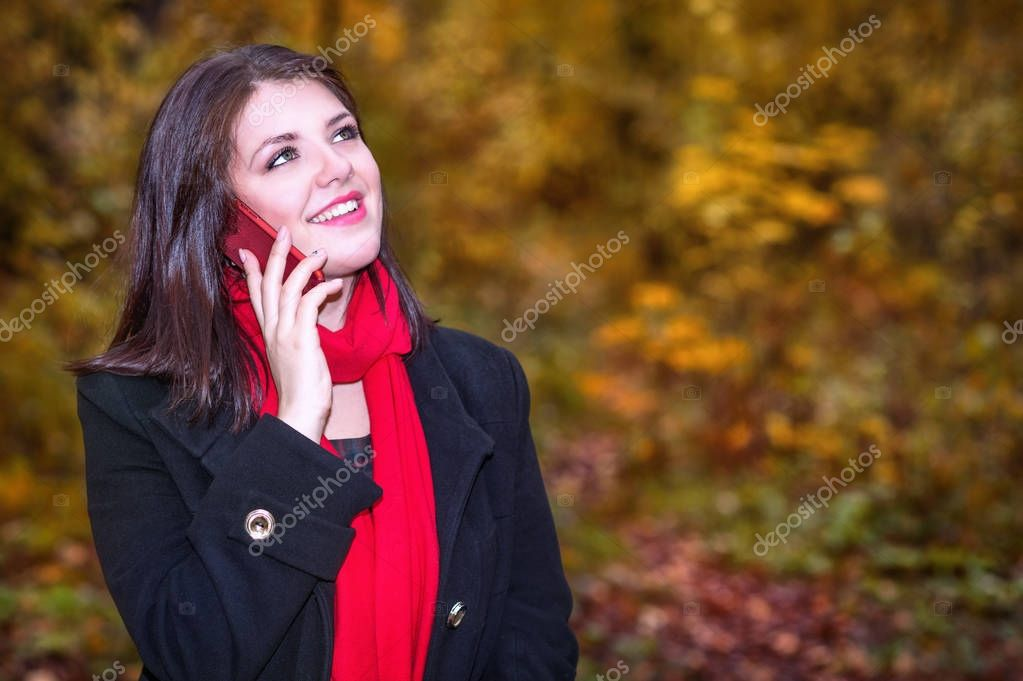 Smiling girl walks in an autumn park and makes a selfie