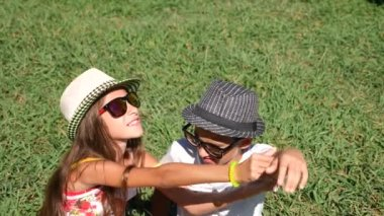 chlapec a dívka, dvojčata 10-12 let sedí na mýtině v parku na letní slunečný den. Radujte se a přijmout. 4k, detail, zpomalené, kopie prostor