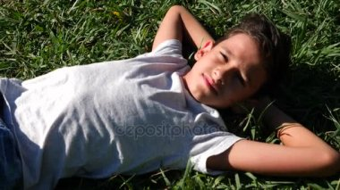 boy 12 years old, lies on a green meadow in a summer sunny day. close-up. Slow motion. 4k