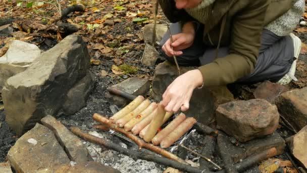 Žena, vaření klobásy na kemp ohně. Turistické smažené klobásy pod širým nebem. 4k