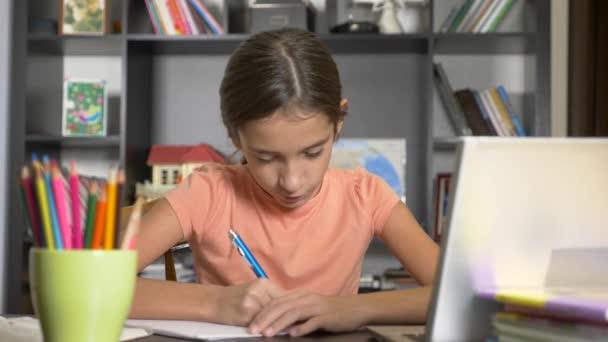 online tanulás fogalmának. a gyerek beiratkozott egy online iskola. a lány csinál házi feladatot a laptop. 4k, lassú mozgás