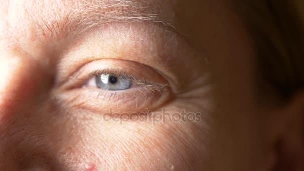 detail, ženské modré oko bez make-up, dlouhé blond řasy a obočí, 4k, pomalý pohyb, kopie ježdění. oko usmívajícího se muže s vrásky