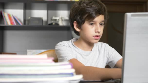 concept of online learning. the child is enrolled in an online school. boy doing homework with laptop. 4k, slow motion
