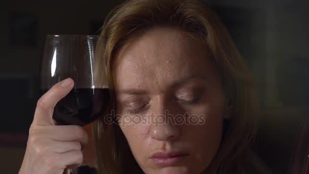 traurige, schöne Frau, die nachts Wein trinkt. Nahaufnahme, 4k, Zeitlupe.