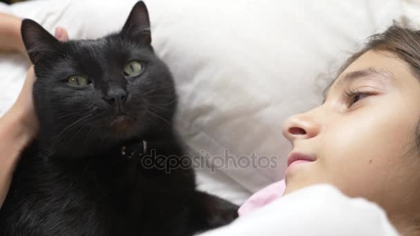 malá holčička objetí a hladí její pet, černá kočka, ležící v posteli. 4k,
