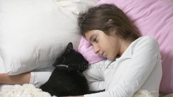 Ein kleines Mädchen umarmt und streichelt ihr Haustier, eine schwarze Katze, die im Bett liegt. 4k,