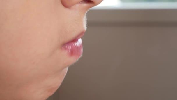Nahaufnahme. Kauend den Mund der Jungen. 4k. der Junge nimmt die Schokolade in den Mund und kaut sie