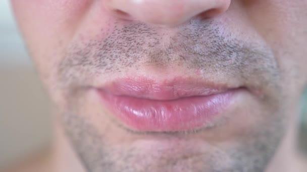 Großaufnahme, männlicher Mund. Der Mann steckt sich den Kaugummi in den Mund und kaut ihn. 4k, Zeitlupe