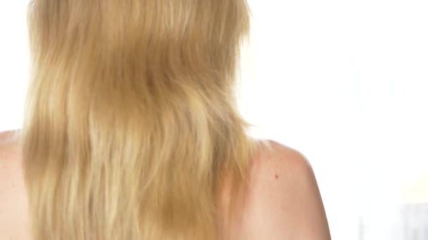 Blick von hinten schöne Frau mit nacktem Rücken, Frisur. Zeitlupe. ruhiges attraktives Mädchen mit langen gesunden Haaren. Schließen. 4k