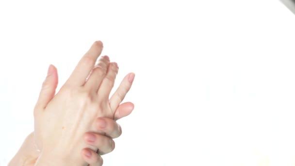Vyčistěte pečlivě upravené ruce mladé ženy použitím krém na ruce, péče o pleť na bílém pozadí. 4 k, Zpomalený, detail