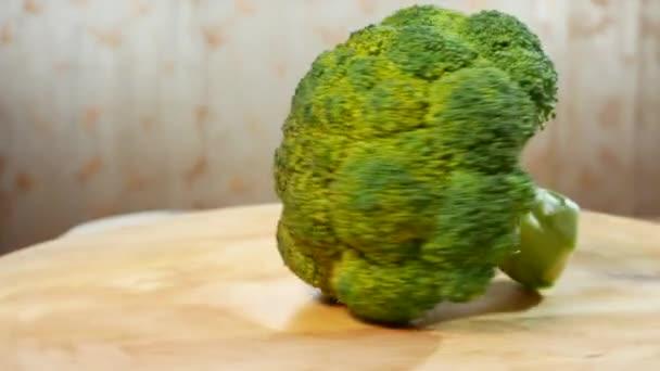 fresh broccoli spinning on a wooden cutting board. 4k.