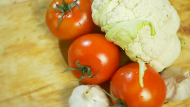 cauliflower and three tomatoes spinning on a wooden cutting board. 4k