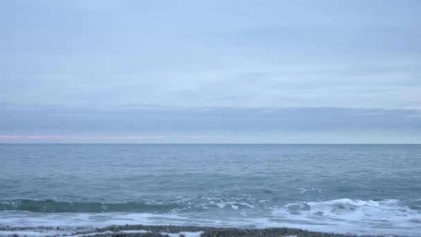 Oblázková pláž při západu slunce. Vlny postříkat a proniknout do kapičky. 4k, pomalý pohyb